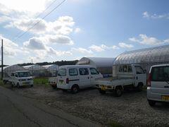[写真]定植作業を手伝ってくれたお母さん達の軽トラックが農園前に集合した様子