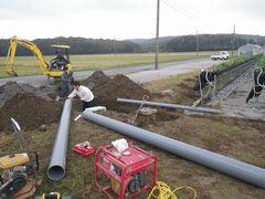 [写真]倒壊したハウスの北東角に、排水管と枡を設置する工事の様子